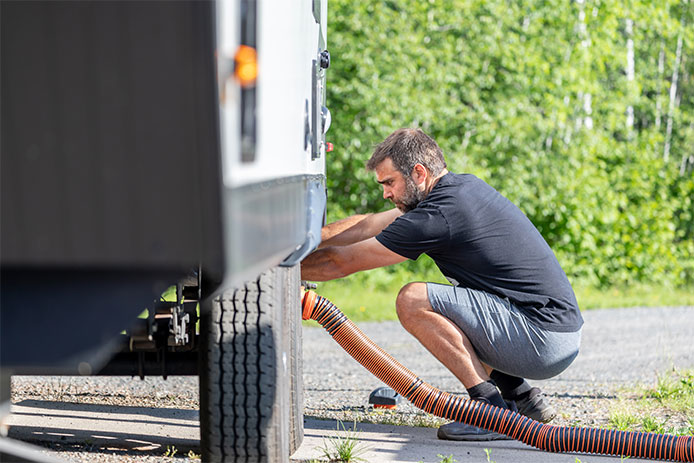Man cleaning out wastewater system in RV